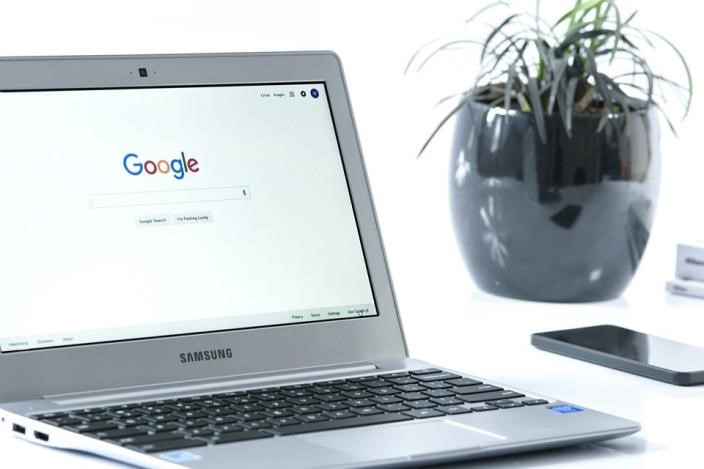 A silver laptop on a white desk next to an indoor plant and smartphone, displaying Google's search engine page